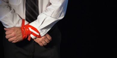 A close up of a man in a suite with his hands tied up with red tape.